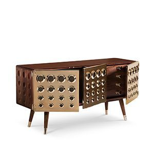 Monocles is a sideboard built entirely out of solid walnut wood, accented by its gold plated brass front doors that feature a protruding circular design. These circles are then engraved to the back and side of the unit, giving it an extreme character and high end look. It is a perfect furniture piece for retro lovers or mid-century admirers, giving the knurling knobs on the drawers or the tapered legs.