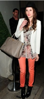 Rosie Fortescue wearing coral skinny jeans, a sheer printed blouse, and a white blazer