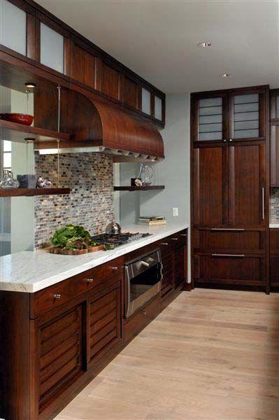 Dark cherry cabinets, light countertops, pretty backsplash.