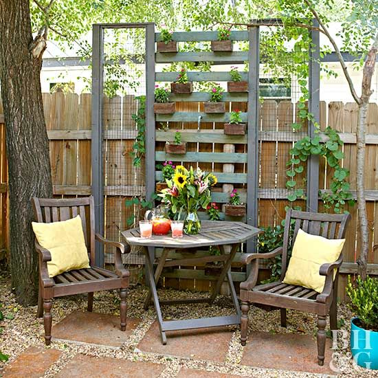 A focal point is a great small yard landscaping idea to draw the eye's attention and help outdoor spaces feel tidy. Here, a simple seating area and vertical planter offers a restful nook.