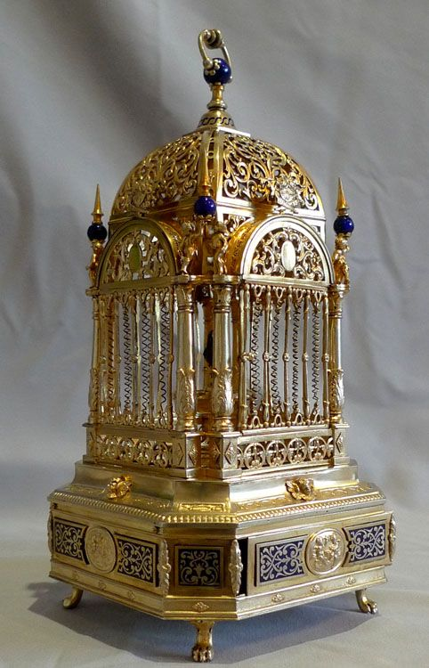 *EXCEPTIONALLY RARE~Silver gilt +enamel singing bird cage of delicate size + of very fine quality.Has canted corners sits on four paw feet + the base is decorated w/inlaid blue enamel in a floral design.To the centre of the four main sides of the base a silver medallion shows two cupids fighting,it is further decorated w/florets,floral corner mounts + cherub heads.The cage itself is held up by 8 decorative collumns w/ acanthus decoration to the base.German or Austro-Hungarian, c.1910.