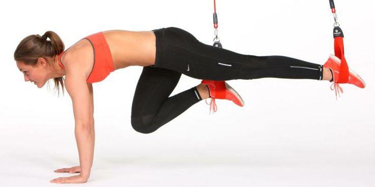 Du trener: Mage og hofteleddsbøyere. Uutgangsstilling: Stå på hendene med anklene i hver sin løkke, 20–30 cm over gulvet. Slik gjør du: Trekk ett kne mot brystet. Strekk ut igjen. Bytt ben og fortsett øvelsen med annenhvert ben. Pass på å holde helt strake hofter i utgangsstillingen og unngå svai rygg.