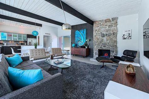 salon blanc, noir et gris avec tableau abstrait et coussins bleu turquoise