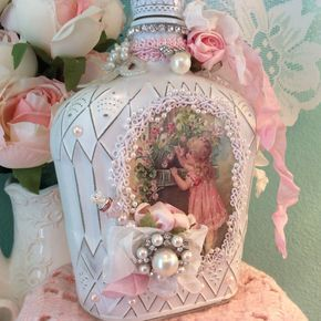 What a beauty! This up cycled bottle has over the top embellishments. Vintage & new jewels with streaming ribbons, trim , pearls and roses. The