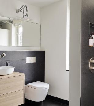 Moderne badkamer met grote tegels, maatwerk meubel en kranen in geborsteld nikkel