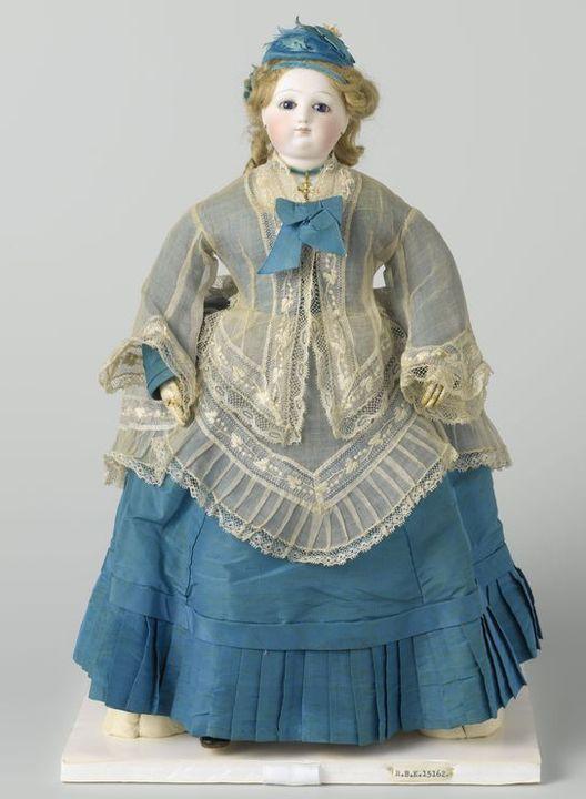 Pop met lang blond gekruld haar  en ledematen van wit glacéleer.  Gekleed in blauw zijden costuum met wit batisten lijf en tuniek,  met bijbehorende hoed en schoenen Anonymous, 1875 h 38.0cm  © Rijksmuseum