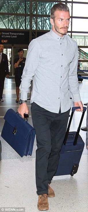 Daddy cool: David wore a grey shirt with a pair of black trousers and brown brogues as he carried his Prada luggage set through the terminal