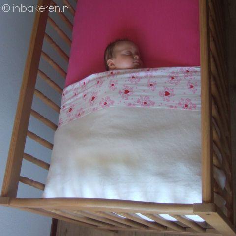 Bedje kort opgemaakt, baby slaapt op haar rug en is voldoende hoog en stevig ondergestopt met laken en deken. Geen knuffels of ander los materiaal in bed.