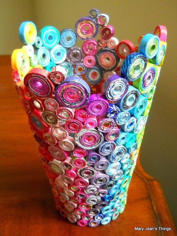 Beautiful vase made news paper, construction paper, and magazines. assembled with a hot glue gun. Just roll up the paper super skinny then flatten it! Use you're new flat ribbon like paper to roll again. Making coin like rolls attach each one to another. the bottom is a giant rolled up papper coin.