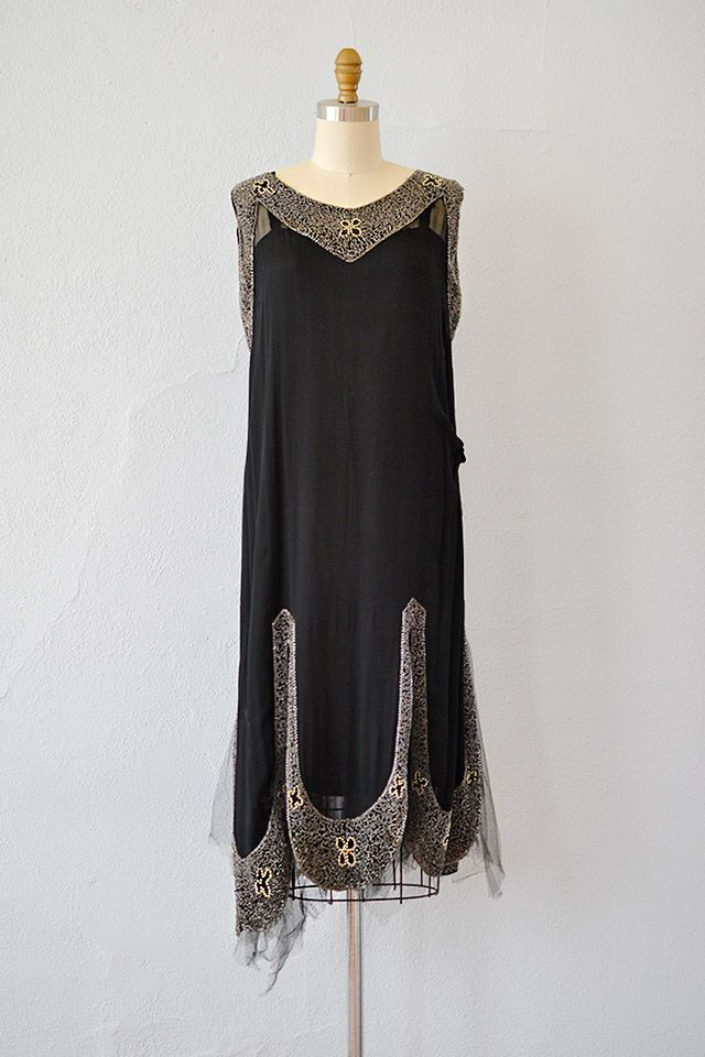 1920s black silk chiffon tabard style dress has black silk tunic worn underneath. Side of the dress has gathered detail. The silver beadwork is really beautiful and there are little pearls too. Has scalloped slit panels that have black tulle net peeking through.