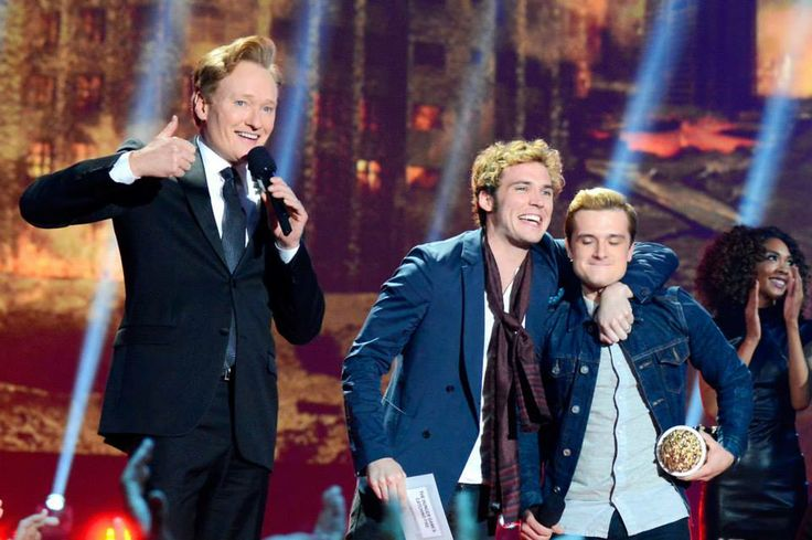 MTV Movie Awards host Conan O'Brien joins Sam Claflin and Josh Hutcherson on stage after The Hunger Games: Catching Fire wins Movie of the Year.