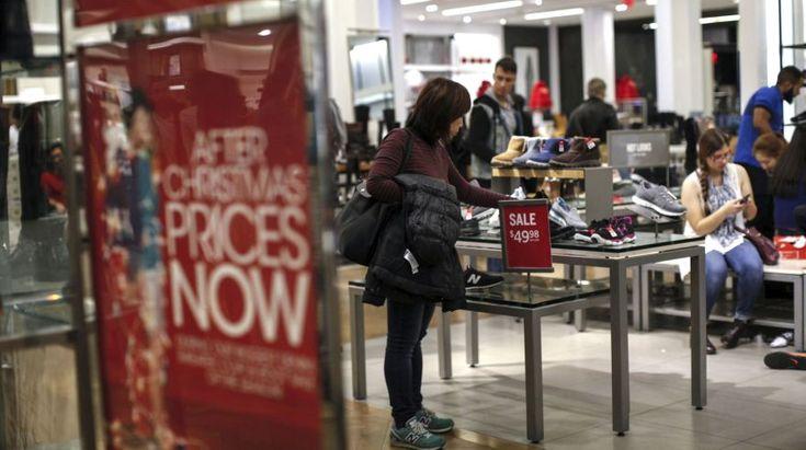 Una mujer mira para un par de zapatos en medio de las ofertas navideñas de la tienda Macy´s en la ciudad de Nueva York, Estados Unidos