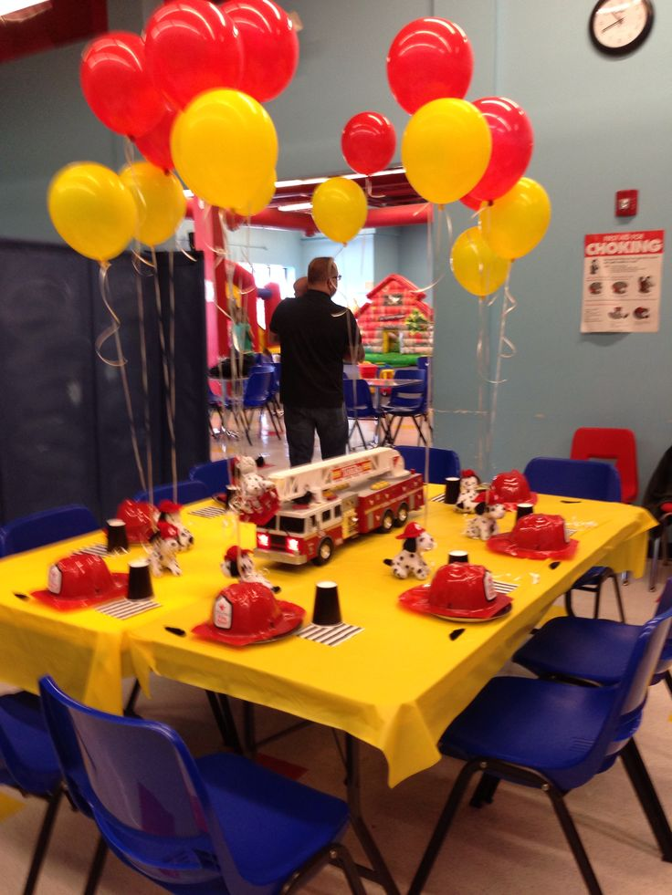 Easy firefighter birthday. Centerpiece is our existing Tonka fire truck. Yellow tablecloth and black tableware from Oriental Trading. Plush Dalmatians from OT with yellow and red balloons. Fire hats with each kid's name (OT) plus fun black mustaches (Party City). Firefighter birthday. Fireman birthday. Fire truck birthday.