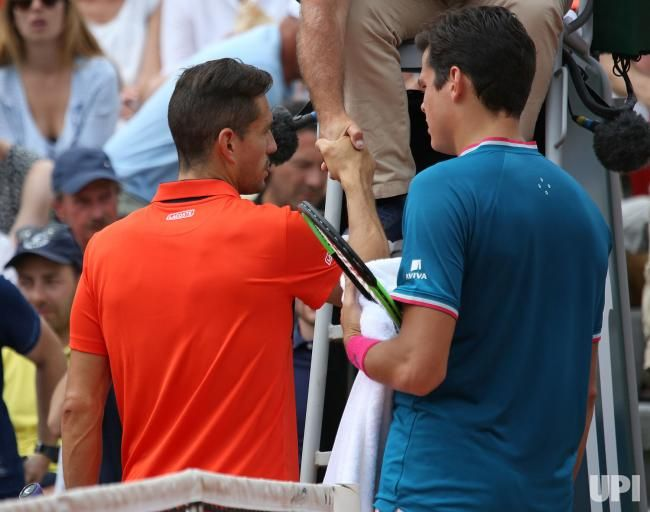 Milos Raonic of Canada (L) meets Guillermo Garcia-Lopez of Spain at the umpire's chair after their French Open men's third round match at…