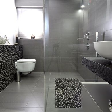 The tiles on the shower floor are repeated on the wall