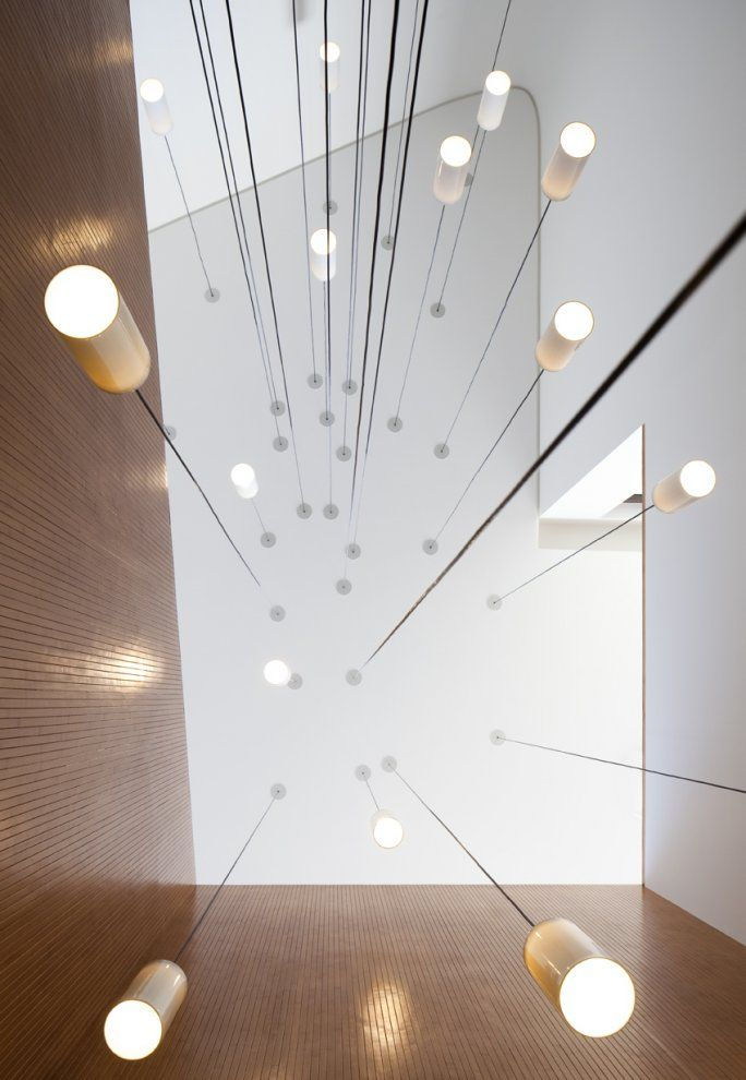 Hanging lights inside the void of the Mop House by AGI Architects. Feels like raindrops of light.