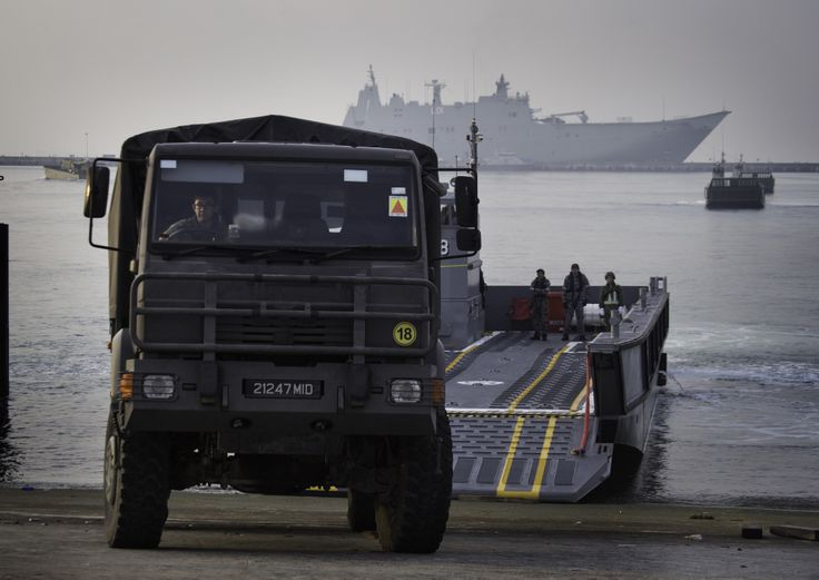 Vehicles are loaded onto LHD Landing Craft from HMAS Adelaide (background) during Humanitarian Aid and Disaster Response training with the Singapore Armed Forces in Changi Bay, Singapore, for Indo Pacific Endeavour 2017.