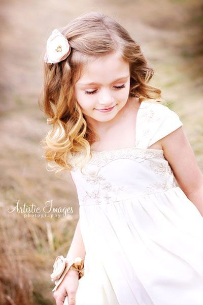 sweet curly flower girl hairstyle with flower both girls could get this look. Might droop if it is hot or humid