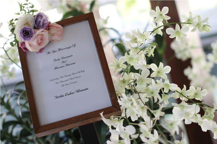 Welcome board adorned with purple Lisianthus, pink and white Rose by Tirtha Bridal Uluwatu Bali