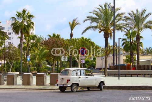 Old retro car in the tropical island scenery with palm trees