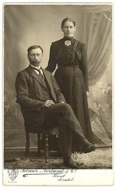 """Fotografi av kvinne med sort """"bykjole"""" pyntet med bolesølje. Telemark Museum anslår at fotoet er tatt 1915 - 1920 - personene på bildet er ikke identifisert. Bildet befinner seg i Bø Museums samlinger."""