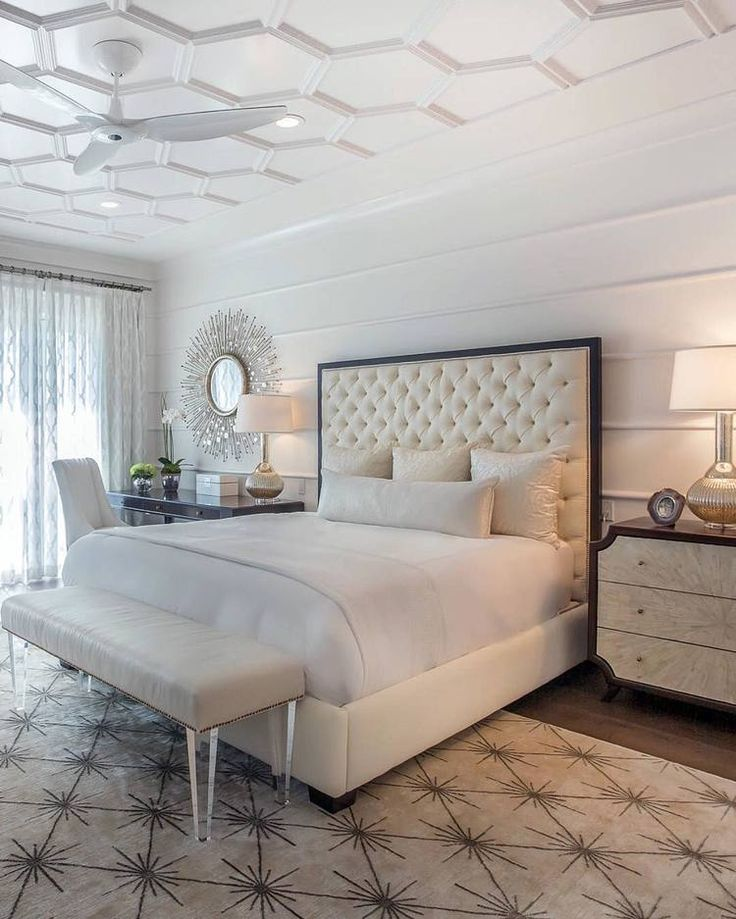 The master bedroom is a symphony of textures and patterns with its horizontal banded walls, hexagonal ceiling design, and furnishings that include a sunburst inlaid bone chest, star bamboo silk rug and quatrefoil sheers. A Bonisolli Photography by Pineapple House
