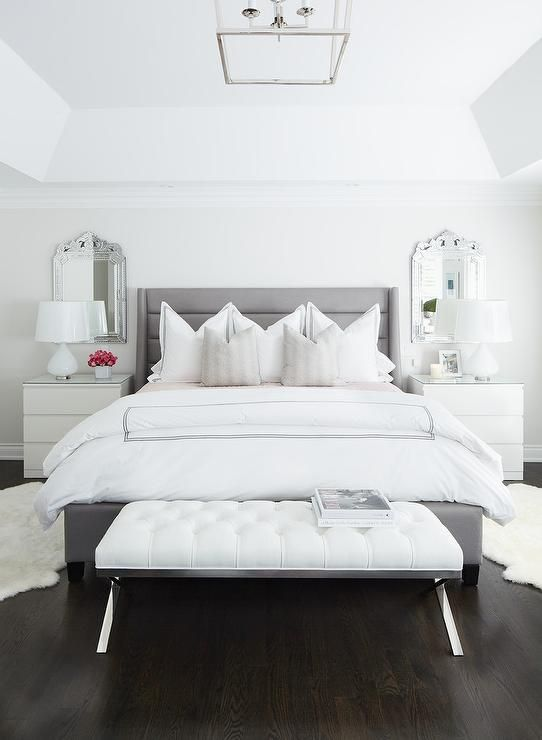 A white leather tufted bench is placed in front of a gray channel tufted bed dressed in white and black hotel bedding and flanked by white sheepskin rugs.