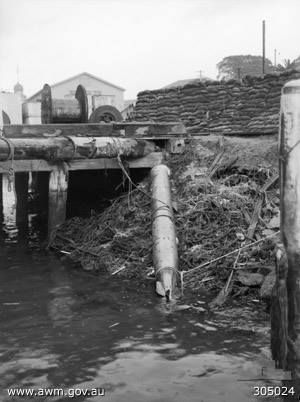 SYDNEY, NSW. 1942-06-10. The spent 17.7 INCH Torpedo, either type 96 or 97, Fired by the unidentified  Japanese midget submarine (known as Midget A), which ran ashore at Garden island during the attack on SYDNEY HARBOUR on 31 MAY 1942. Note the blast wall of sandbags in the background, constructed prior to the torpedo being dragged further in.  (NAVAL HISTORICAL COLLECTION). Date10 June 1942.