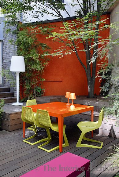 What was a dark and sombre urban courtyard has been transformed with raised decking and colourful contemporary furniture.