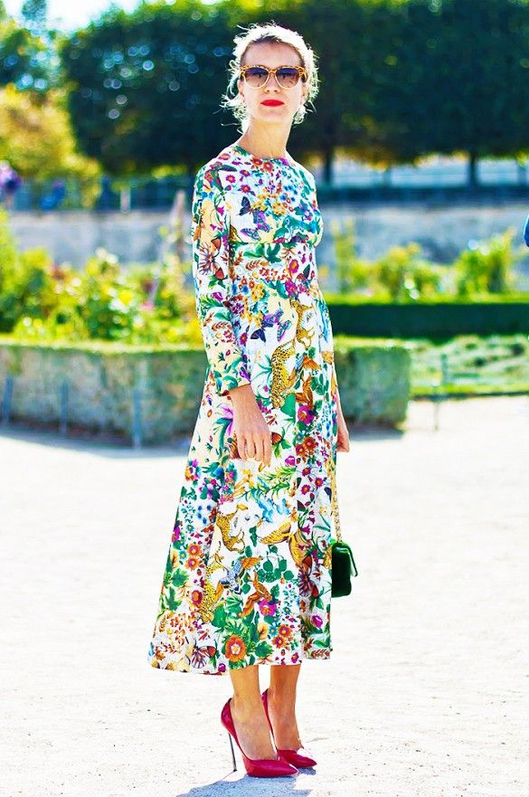 Natalie Joos wears a floral dress with a midi hem and accessorizes with pink heels and a velvet mini bag