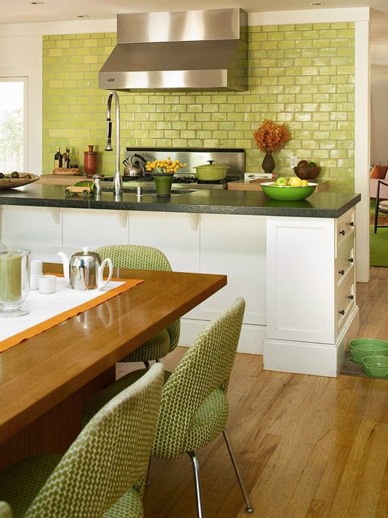 Green glass subway tile adds a dash of excitement to this open kitchen.