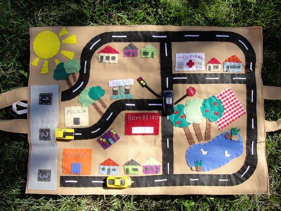Pista em feltro para carrinhos 50x70 cm (aberta), paisagem urbana com garagem, semáforo, lago, escola, etc. Quando fechada torna-se uma sacola com bolsos para guardar os carrinhos. Carrinhos não inclusos. R$ 98,00