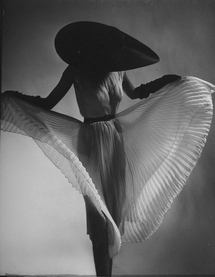 Model dorian leigh sporting black picture hat while showing off accordian pleats of a straight hanging sheer dress jane derby which can swirl into a
