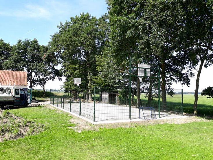 Mini voetbalkooi 7.5 x 15 meter met basketbal in Kraggenburg. Wanden groen, doelen blauw en de antivandaal basketbalborden wit.