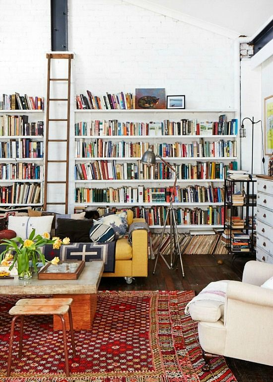 In loooooove! Great books, floors, sofa (maybe in kelly green or turquoise and with less pillows&throws though), cool rugs and light, a ladder for the top books, and painted brick walls. Awesome loft :)