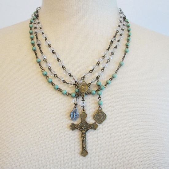 """Three Strand Cross Necklace  Three delicate strands of beads all strung with eye hook chain for more detail. One large crucifix with two smaller saint medallions. One strand of mint green color beads and two clear. Adjustable lobster claw clasp.  19"""" long with 2"""" cross"""