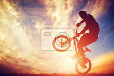 Canvas of Poster Man rijdt op een BMX fiets uitvoeren van een truc tegen zonsondergang hemel