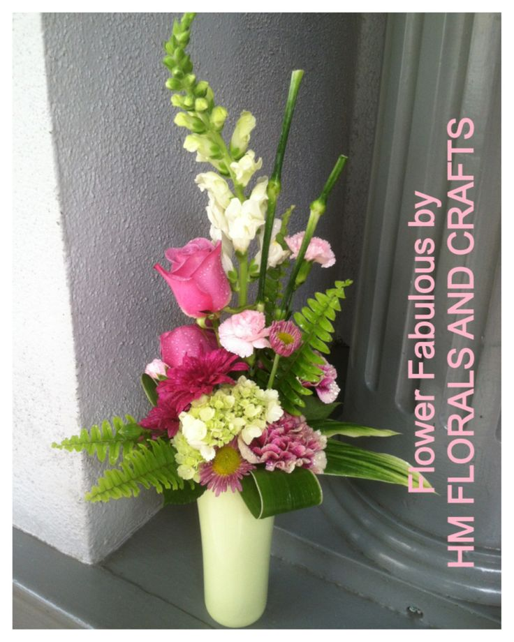 A slim arrangement in green and pink. I like the use of the carnation stems