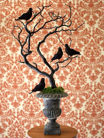 """Spooky Still Life. Make ordinary objects a little creepier with a coat of black paint. Just a few simple steps and this discarded tree branch becomes a scary perch for menacing ravens. Find a tree branch (the more twisted and gnarled, the better) and spray-paint it black. Once dry, insert the branch in an urn or pot. Finish by placing a few black ravens on the branch."" ""Creepy Halloween Decorations."" Better Homes and Gardens."