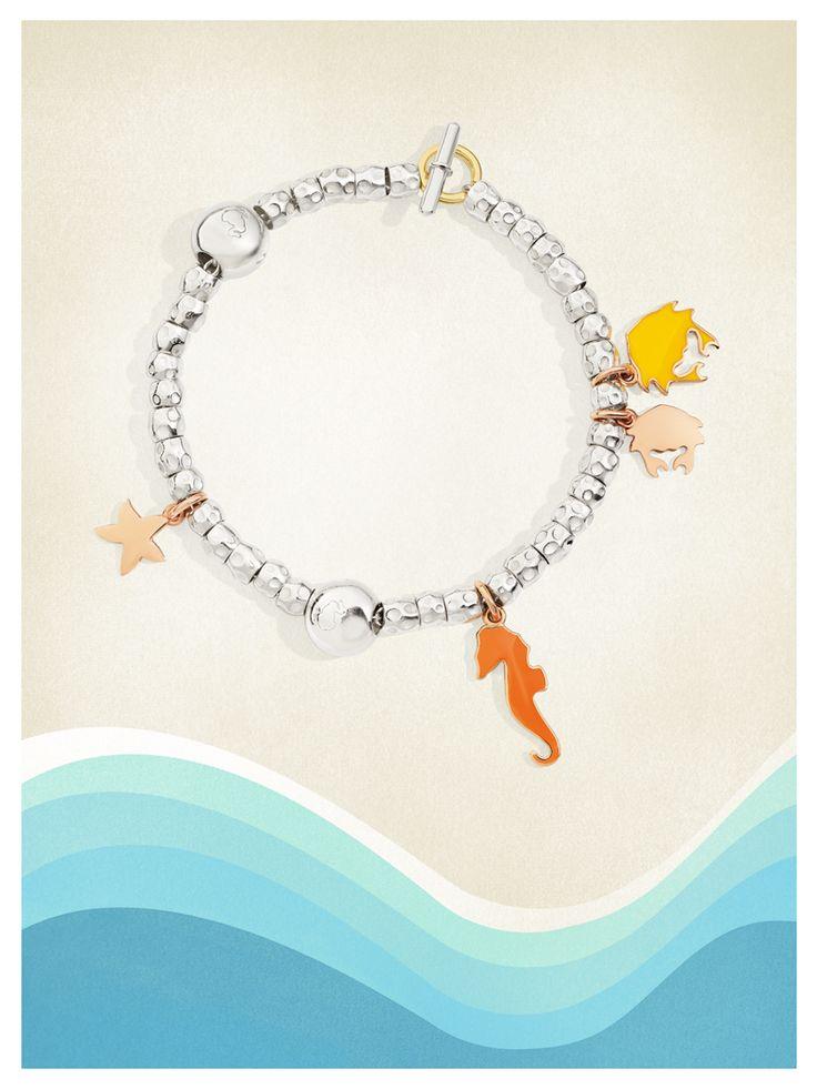Dodo's silver bracelet composed with the 9kt rose gold crab and starfish charms and the yellow and orange enamel crab and seahorse charms.