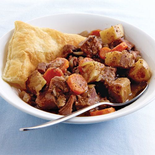 """This simple version of the classic Irish dish has the distinctive bitter flavor of Guinness stout. Although it's slow-cooked, the hearty beef stew requires minimal prep time. When it's ready, the puff pastry """"tops"""" are baked separately and served alongside."""