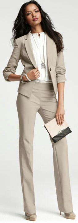 Light taupe/stone pant suit with long sleeved jacket, notched collar and one button. The slim trousers have a wide waistband. Suit worn with stunning white shirt: very high split standup neckline. Taupe two-tone high-heeled pumps. Square clutch, white with a swipe of black at the bottom. Style Planet