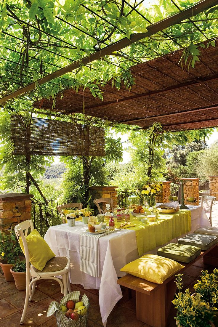 Dining al fresco is the ultimate visual and food experience. This setting uses two table clothes one covering the table, another going cross wise to add the colors yellow and green which are emphasized by the pillows, fruit and flowers. (source elmueble) Review by www.palmbeacheshomestaging.com