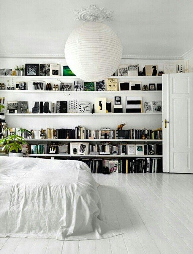 Repisas, libros, cama, planta, blanco y negro.