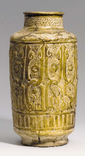 "A LARGE KASHAN LUSTRE MOULDED ALBARELLO CENTRAL PERSIA, EARLY 13TH CENTURY Of cylindrical form on small foot, sloping shoulder rising to a vertical neck with everted mouth, sides moulded with a large kufic inscription, tall hastae knotted together, on a ground of tight scrolling vine, a band below of simple vertical bands, shoulder with a bands of running animals reserved against a lustre ground, neck with simple scrolling motifs, the interior with bold stylised kufic, 14¾"" high"