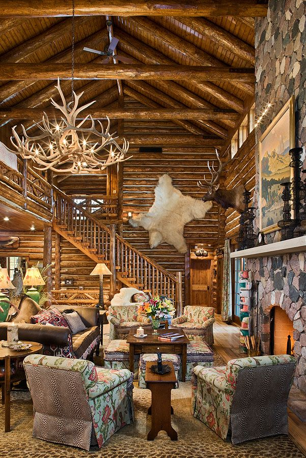 Great room has soaring ceilings with log rafters and log ties.  The masonry fireplace provides plenty of warmth to the room.  A structural log stair system leads to the second level.