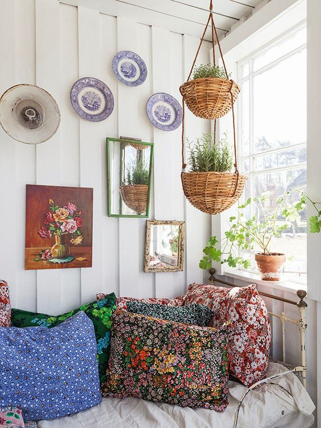 hanging plant baskets, cusions, picture wall.