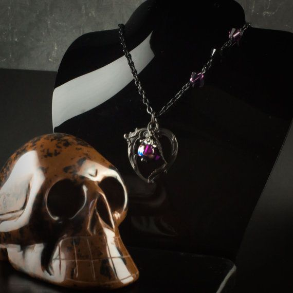 20″ Goth inspired pendant necklace with three Swarovski bicone crystals of purple and black inlaid into the black chain. The antique rubbed black brass flourish heart and leaf charm is complimented by a dark purple glass luster bead. A dark but beautiful arrangement.