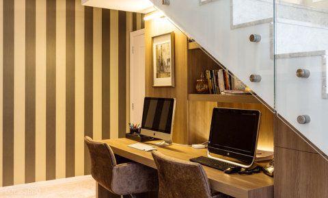 A solução de aproveitamento dessa cobertura duplex foi transformar o espalo em um escritório para o casal. Os módulos em madeira e coluna com gravuras são armários que ficam camuflados, aproveitando todos os espaços. Prateleiras iluminadas e papel de parede completam o ambiente. Projeto de Karina Koetzler.