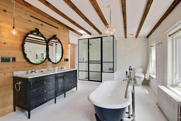 White, black, and wood bathroom with exposed ceiling beams, two mirrors and freestanding tub
